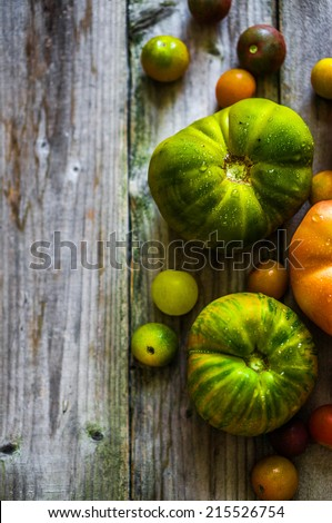 Heirloom tomatoes on rustic background - stock photo