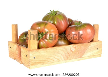 heirloom tomatoes on vine in wooden crate isolated on white background