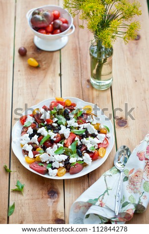 Heirloom tomatoes salad with cheese on wooden surface - stock photo