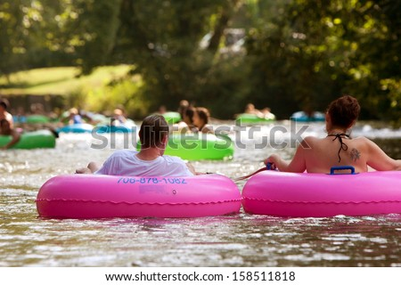 HELEN, GA - AUGUST 24:  A couple enjoys tubing down the Chattahoochee River with hundreds of others in North Georgia on a warm summer afternoon, on August 24, 2013 in Helen, GA.  - stock photo