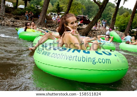 HELEN, GA - AUGUST 24:  A teenage girl flashes a peace sign as she tubes down the Chattahoochee River with hundreds more people on a warm summer afternoon, on August 24, 2013 in Helen, GA.   - stock photo