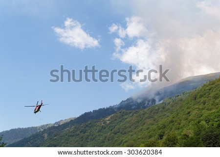 Helicopter fighting big mountain fire - stock photo