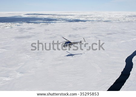 Helicopter flying above the sea ice in the Weddell Sea, Antarctica - stock photo