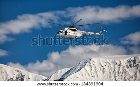helicopter flying on the background of snow-capped peaks of the mountains - stock photo