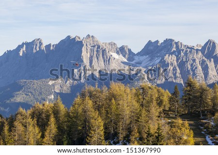 Helicopter flying over the forest and mountains - stock photo