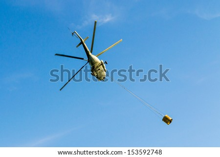 Helicopter in action carrying water bucket.  - stock photo