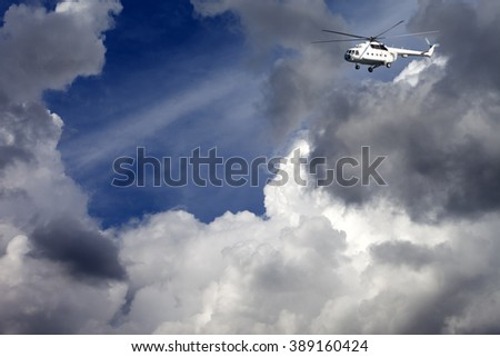 Helicopter in blue sky with clouds at sun day - stock photo