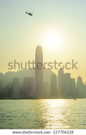 Helicopter in Hong Kong sky at sunset - stock photo