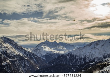 Helicopter in the snowy Alps - stock photo