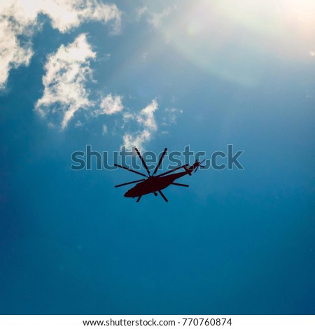 helicopter is flying across the sky