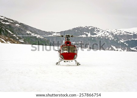 Helicopter landing on glacier in between snowy mountains for glacier tours during the winter months. - stock photo