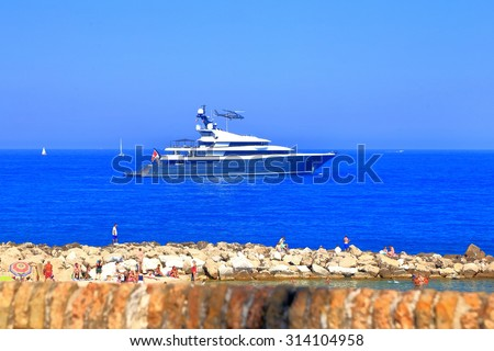 Helicopter landing on luxury yacht anchored outside Antibes harbor, French Riviera, France