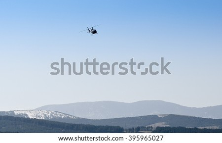 Helicopter low flying over mountain hills