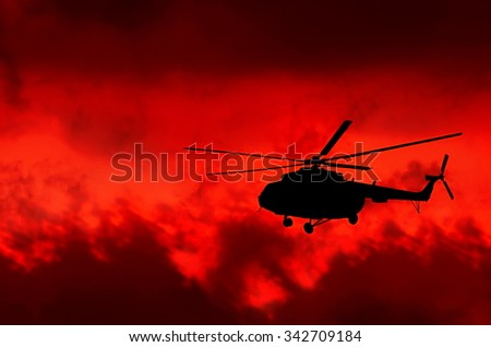 helicopter on a background of fire sky - stock photo