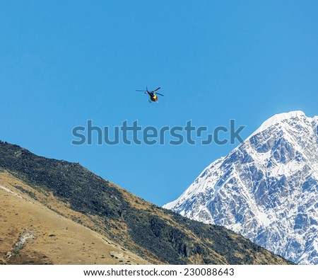 Helicopter on background of the Nuptse wall - Everest region, Nepal, Himalayas