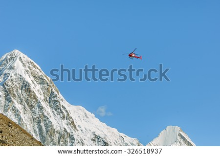Helicopter on background of the Pumo Ri in the Mahalangur Himal ridge - Everest region, Nepal, Himalayas