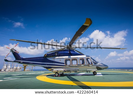 Helicopter or chopper land at oil and gas platform accommodation area for receive and sent passenger from onshore hangar to offshore platform  - stock photo