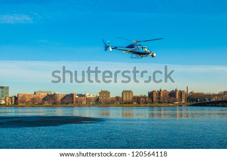 Helicopter over the Charles River with Cambridge in background - stock photo