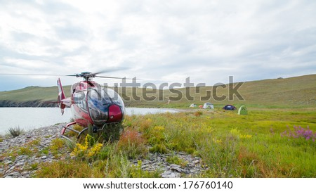 Helicopter parked and individual camp - stock photo