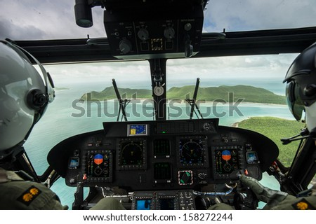 Helicopter pilot seen from behind above the island, Thailand - stock photo