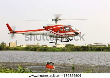 Helicopter refill bucket in lake for fire fighter  - stock photo