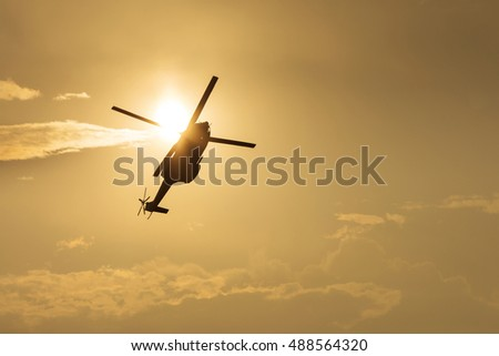 Helicopter silhouette flying in the cloudy sky, stunt aerobatic show, sunset and sun rays.