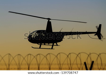 helicopter silhouette in flight over barbed wire fence