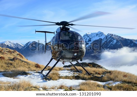 Helicopter waiting for hunters in South Westland's Southern Alps, New Zealand - stock photo