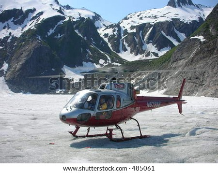 helicopter with snow capped mountains alaska