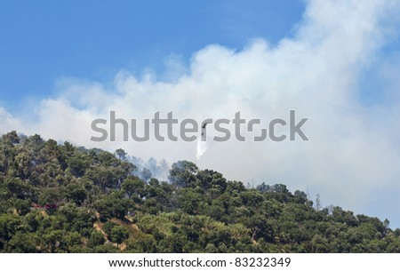 Helicopter working in extinguishing forest fire, using water, on the mountain - stock photo