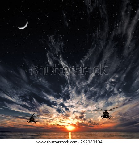 Helicopters Mi-8, warm sunset, moon and starry sky - stock photo