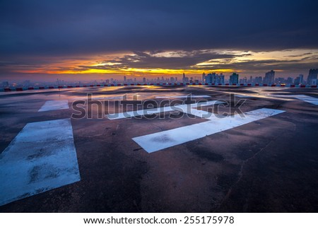 Helipad on the roof of a skyscraper after rain with cityscape view - stock photo