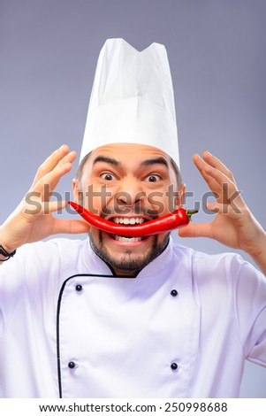 Hell kitchen. Closeup portrait of handsome funny cook holding red pepper in his mouth while standing over grey background with copy space - stock photo