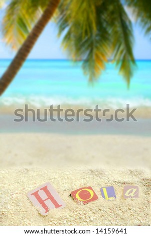 hello in spanish, hola on a mound of sand on a tropical beach with palm tree and ocean in the background - stock photo