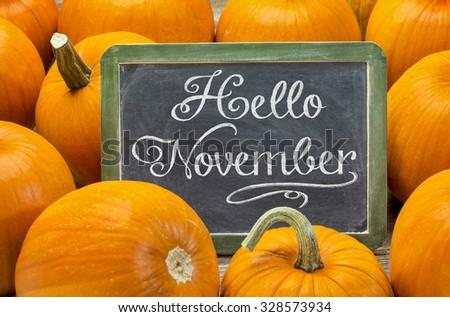 Hello November - white chalk handwriting on a vintage slate blackboard surrounded by pumpkins, Thanksgiving greetings - stock photo