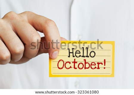 Hello October! Businessman holding a card with a message text on - stock photo