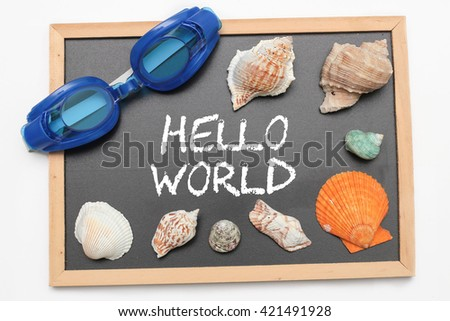 Hello World text on chalk board with swimming goggle and shell - vacation and business concept - stock photo