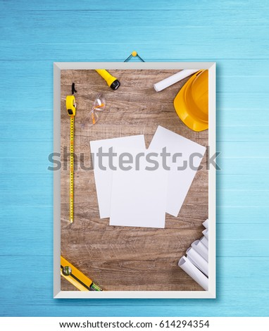 Helmet, flashlight and tape measure. Architecture plans and protective glasses. White sheet of paper. Building level. Photo frame on wooden rustic wall.