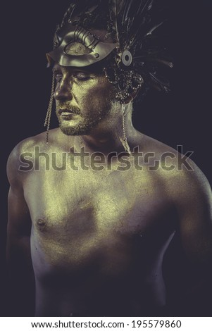 Helmet, Man with body painted gold feather mask and steel sword - stock photo
