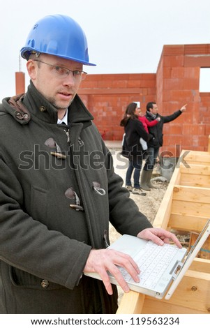 helmeted architect in construction site using laptop - stock photo