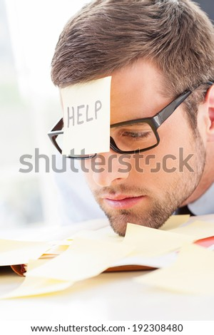 Help! Frustrated young man in formal wear with adhesive note on his forehead leaning his head at the table - stock photo