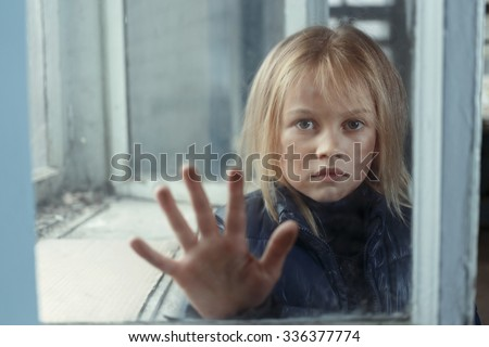 Help me. Little poor miserable girl  standing near window and begging for help while  holding her hand on glass - stock photo