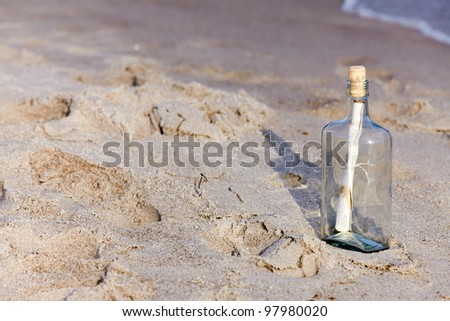 Help message in a bottle on beach - stock photo