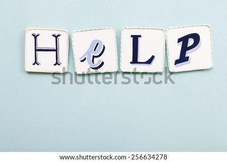 Help signboard. Handwritten colors letters word. Light blue background. Calligraphy and lettering fine art.