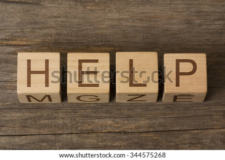 HELP text on a wooden background - stock photo