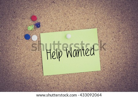 Help Wanted written on sticky note pinned on pinboard - stock photo