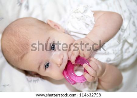 Help with teething. Teething toy in baby mouth - stock photo