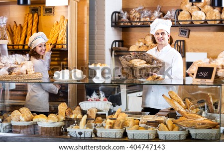 Helpful bakery staff offering bread and different pastry for sale