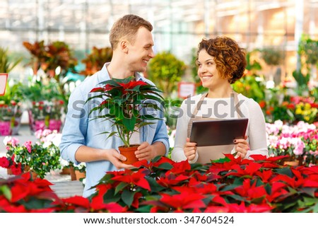 Helpful employee. Young attractive florist is helping male customer to choose a particular flower.