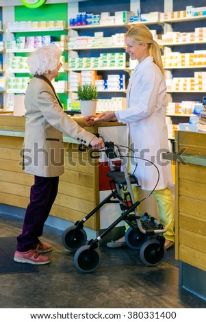 Helpful female pharmacist in white lab coat standing at pharmacy counter with elderly customer using wheeled walker - stock photo